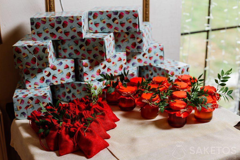 Dárkové krabičky zabalené do barevného papíru, červené jutové tašky a sklenice s konzervami