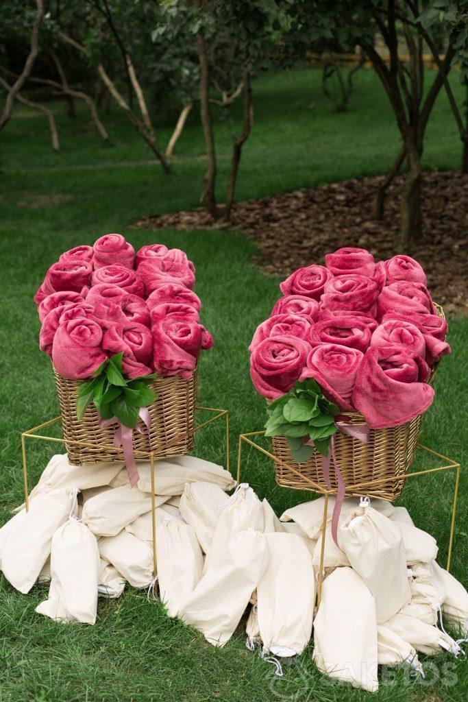 Dekorativně srolované přikrývky a pantofle v plátěných sáčcích připravených pro svatební hosty