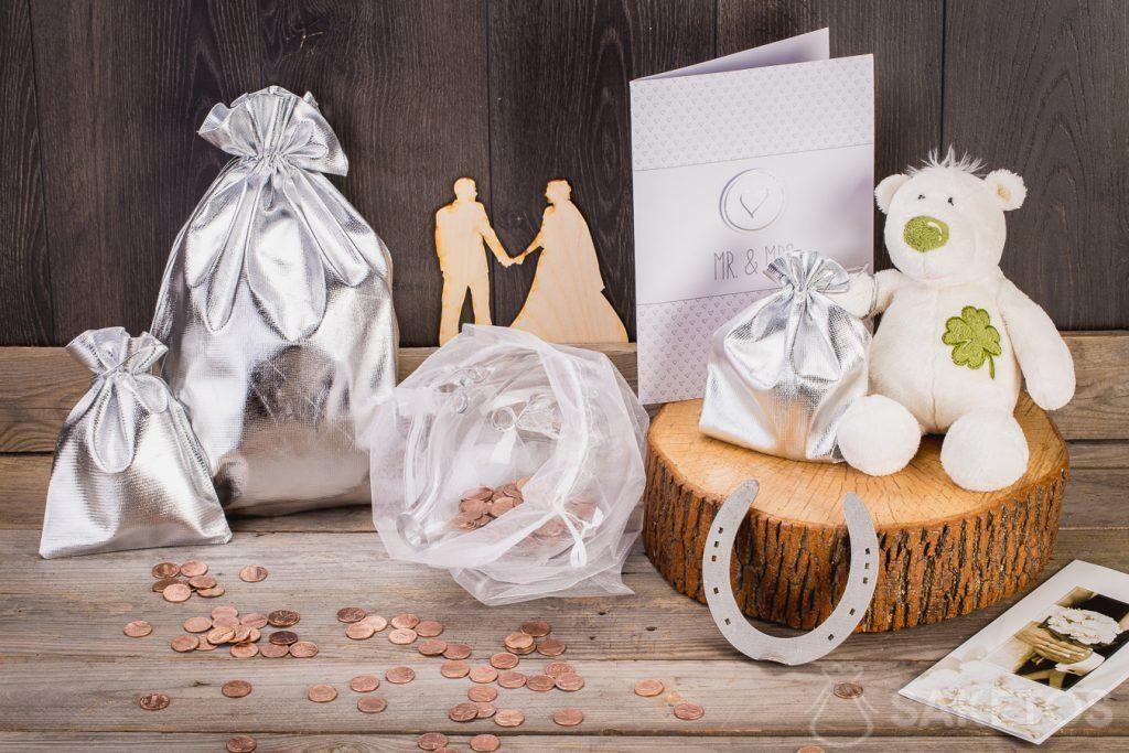 Když má svatební dar mít peníze, můžete si je zabalit do skleněné prasátko v sáčku organzy.