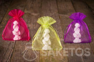 Figurky andělů zabalené v barevném organzovém sáčku určené jako poděkování svatebčanům