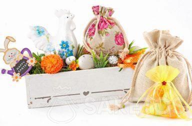 Barevné velikonoční kompozice z látkových sáčků a obdélníkového květináče s velikonoční vajíčkami.