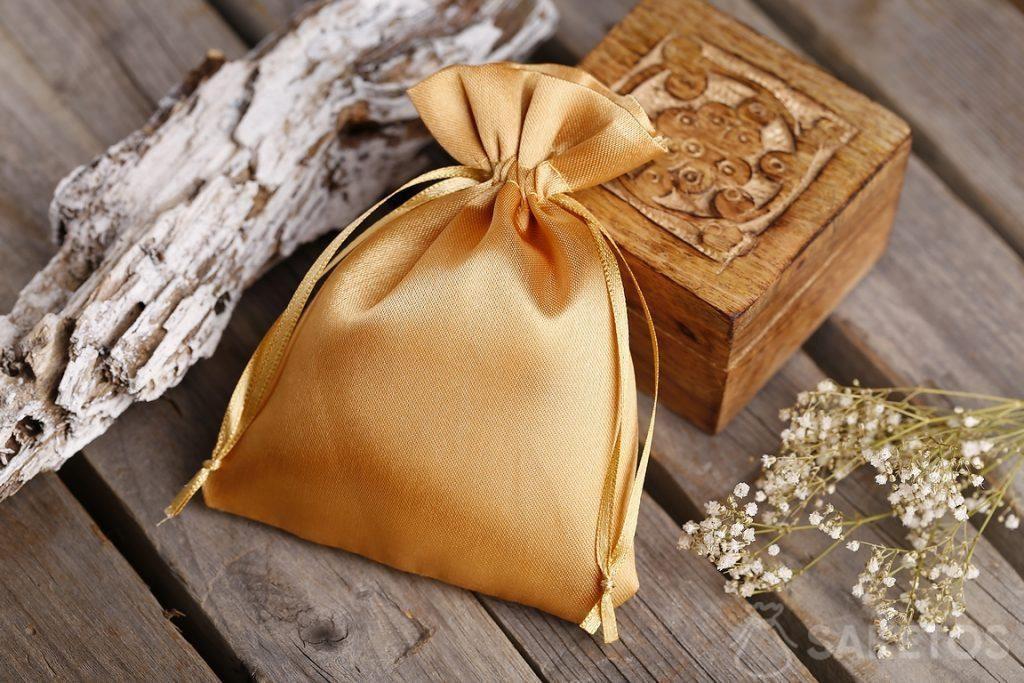 Zlatý saténový sáček a malá dřevěná krabička na suvenýry