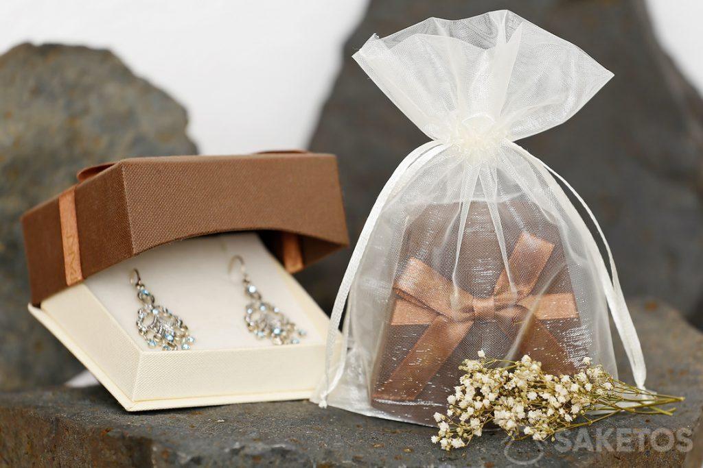 Stříbrný saténový sáček jako elegantní balíček kartonové šperkovnice s náušnicemi.