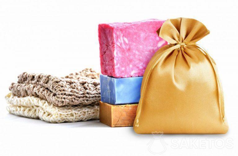 Zlatý saténový sáček na pozadí barevných mýdel.