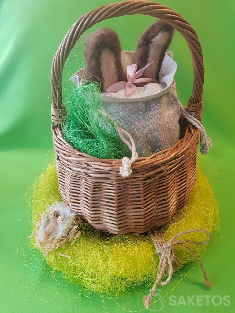Košík s plátěnou taškou, ze které vyčnívají uši plstěné bunny vlny.