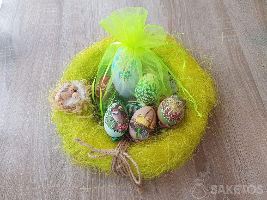 Ručně malované velikonoční vajíčka v neonově zelených organzových sáčcích.